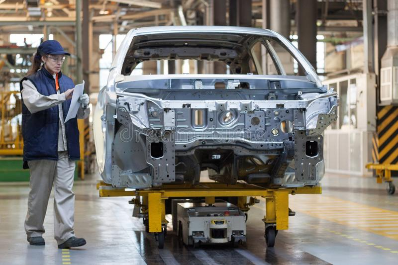 Rússia, Izhevsk - 15 de dezembro de 2018: LADA Automobile Plant Izhevsk O trabalhador fêmea verifica o corpo de um carro novo foto de stock royalty free