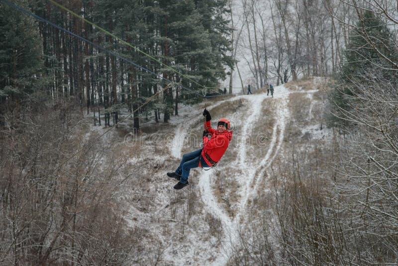 Rússia, Izhevsk - 18 de novembro de 2018: Zipline Homem que desliza no trole da corda sobre a ravina na alta altitude Extremo e imagem de stock royalty free