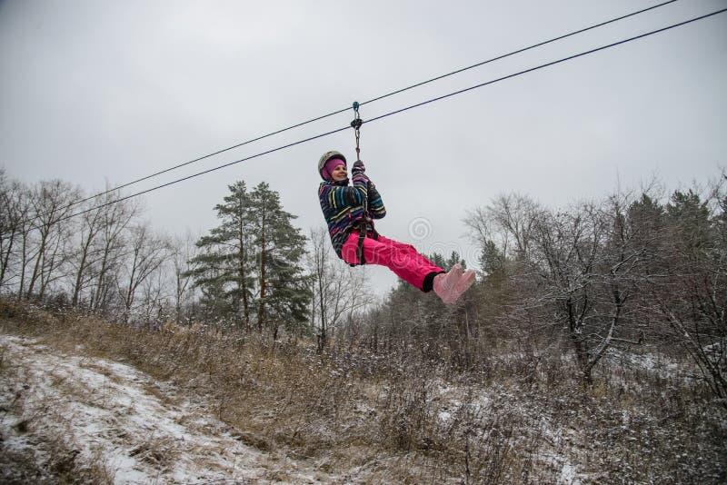 Rússia, Izhevsk - 18 de novembro de 2018: Zipline Mulher que desliza no trole da corda sobre a ravina na alta altitude Extremo e foto de stock