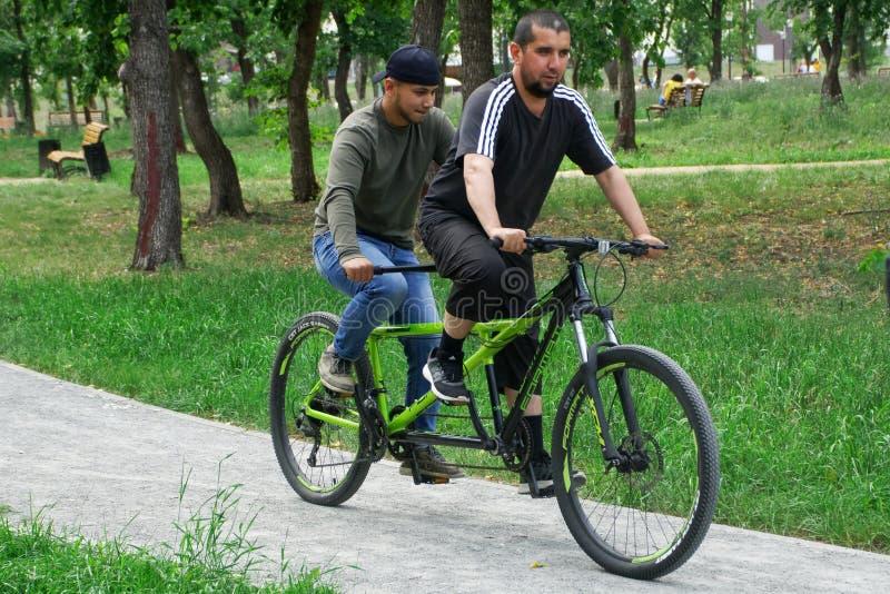 Rússia, Magnitogorsk, - julho, 31, 2019 Dois homens que montam uma bicicleta em tandem através do parque da cidade Caminhada do v fotos de stock royalty free