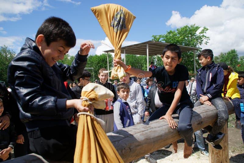 Rússia, Magnitogorsk, - junho, 15, 2019 Os meninos estão lutando sacos em um log durante o feriado Sabantuy Jogo nacional fotografia de stock