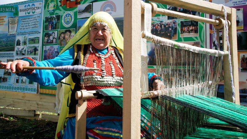 Rússia, Magnitogorsk, - junho, 15, 2019 Uma mulher idosa com um eixo senta-se atrás de um tear do artesanato O participante do imagens de stock royalty free