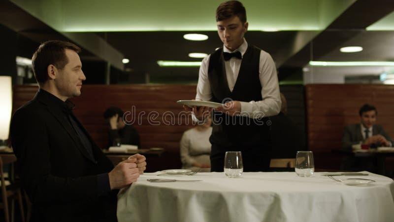 Rússia, Moscou - em maio de 2018: O garçom serve o homem de negócios no restaurante estoque O garçom traz o alimento para fotografia de stock royalty free