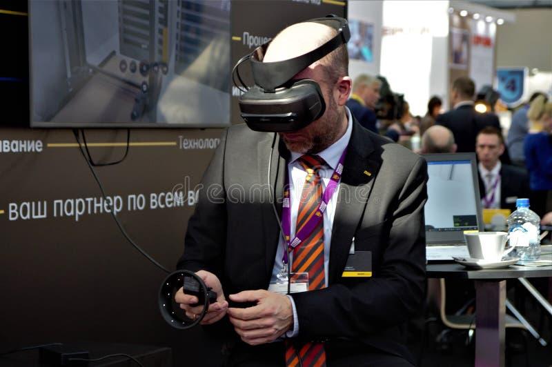 03 14 2009 Rússia, Moscou Padaria moderna Moscou da exposi??o, Expocentre homem em uns auriculares do negócio VR imagem de stock
