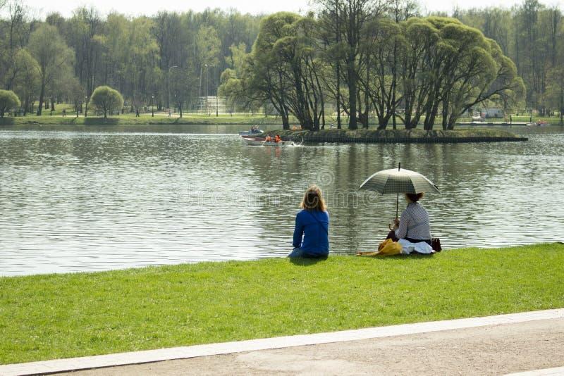 01-05-2018, Rússia, Moscou, solar do parque de Tsaritsyno, feriados no parque, mulheres de maio está descansando no lago em um gr imagens de stock royalty free
