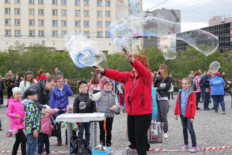 Rússia, Murmansk - 24 de junho de 2018: a celebração do dia da juventude de Rússia, a menina começa bolhas de sabão foto de stock