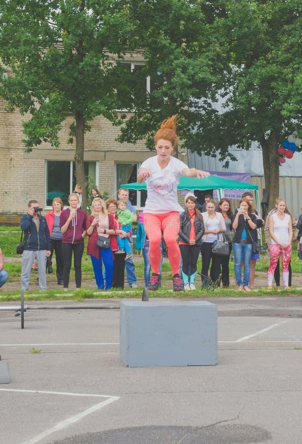 Rússia Nikolskoe competição do julho de 2016 na menina atlética do crossfit com cabelo vermelho salta no freio foto de stock