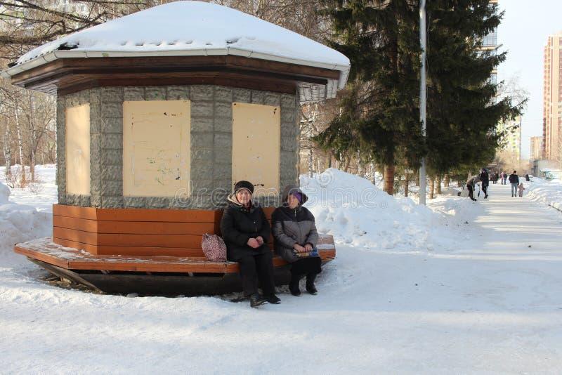 Rússia, Novosibirsk, o 23 de fevereiro de 2019: duas mulheres idosas que sentam-se em um banco no parque no resto do inverno imagens de stock