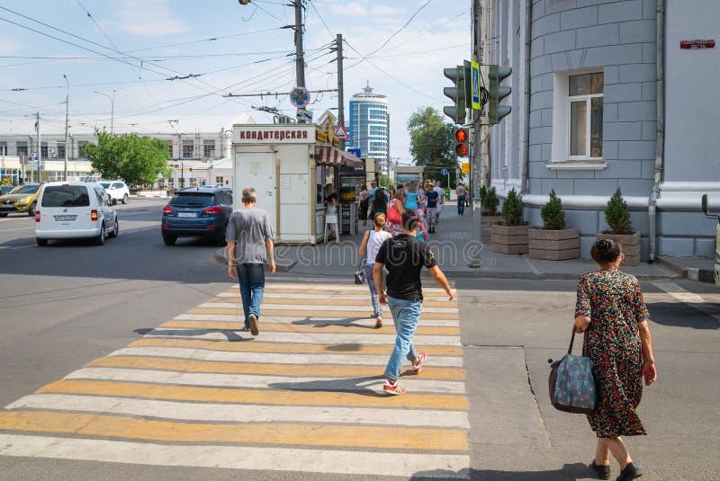 Rússia, Rostov On Don, o 28 de junho de 2018: Os povos cruzam a estrada a um sinal vermelho Violação de regras de tráfego Perigo  foto de stock