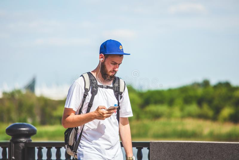 Rússia Rostov-On-Don turista do indivíduo do 16 de junho de 2018 escuta a música no telefone e anda em torno da cidade, onde o ca imagem de stock