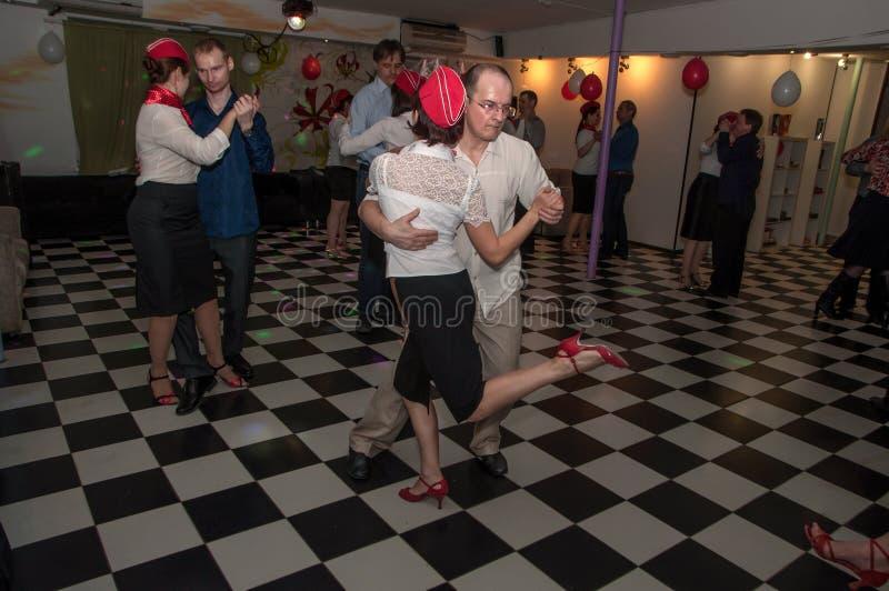 Rússia, Ryazan - 20 de fevereiro de 2017 - alguns pares felizes que dançam o tango no estúdio de dança fotografia de stock