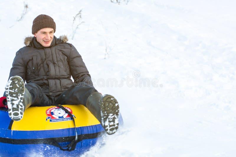 Rússia, Ryazan 5 de janeiro de 2019: homem feliz que desliza abaixo do monte nos tubos da neve sobre o fundo natural do inverno fotografia de stock