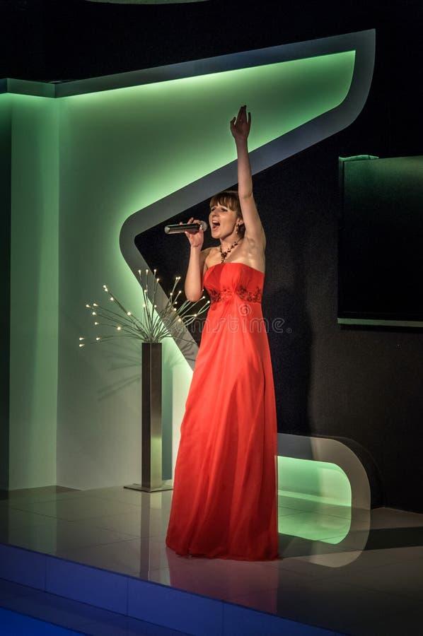 Rússia, Ryazan - 30 06 2014: Posição bonita da menina com o microfone que canta passionately com olhos fechados imagens de stock royalty free