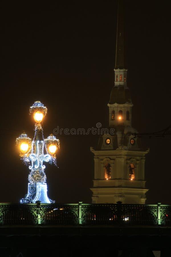 Rússia, St Petersburg, uma lanterna na ponte da trindade no fundo do Peter e do Paul Fortress fotos de stock