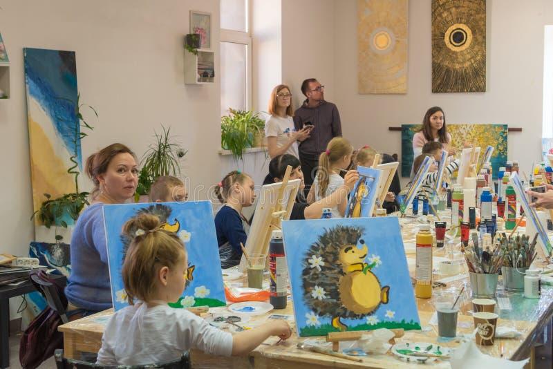 Rússia, Tartaristão, o 21 de abril de 2019 Classe de tiragem das crianças Armação, lonas, pinturas na tabela Um grupo de tração d imagens de stock
