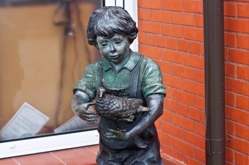 RÚSSIA, ZELENOGRADSK - 11 DE OUTUBRO DE 2014: Escultura de um menino com o pássaro no passeio de Zelenogradsk imagens de stock royalty free
