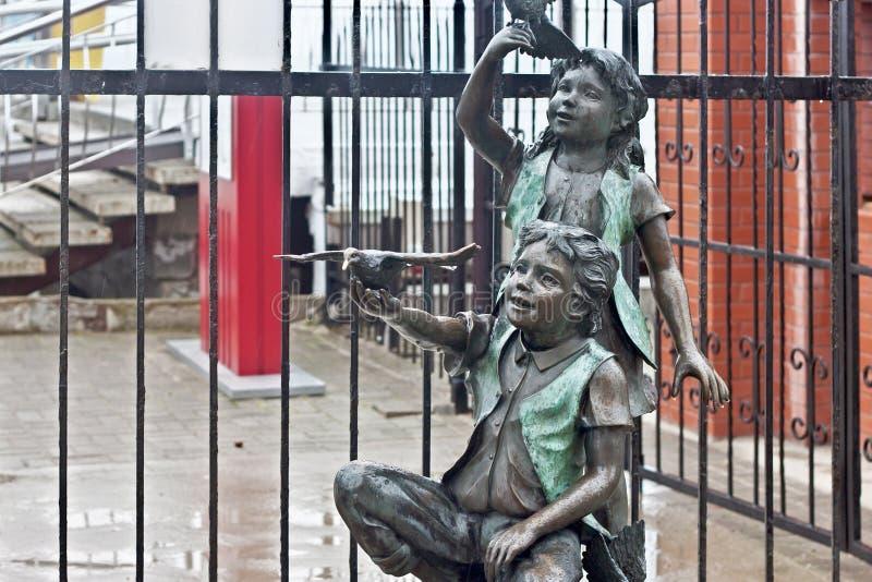 RÚSSIA, ZELENOGRADSK - 11 DE OUTUBRO DE 2014: Escultura de um menino e de uma menina fotografia de stock