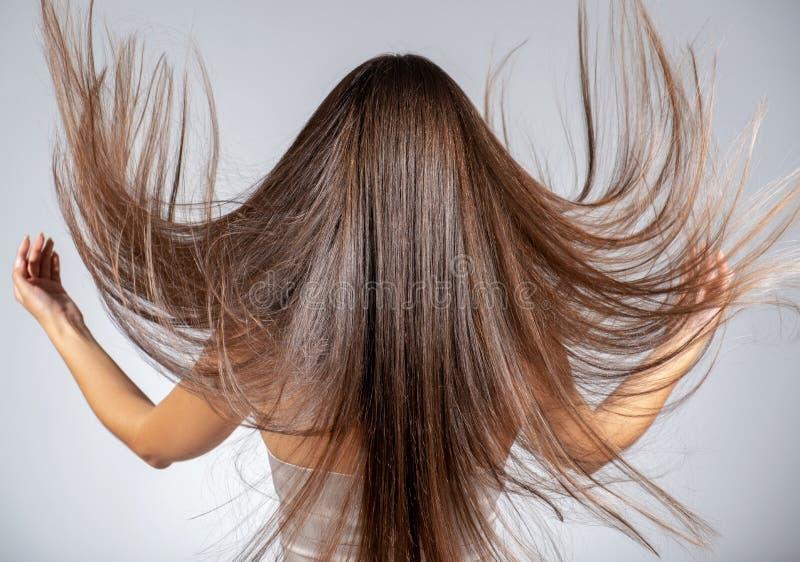 Rückansicht einer Brunette-Frau mit langgestrecktem Haar stockbild