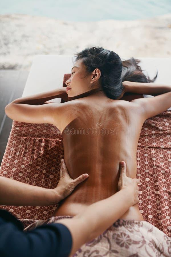 Rückenmassage am thailändischen Badekurort Frau, die Körper-Massage am Salon hat stockfotos