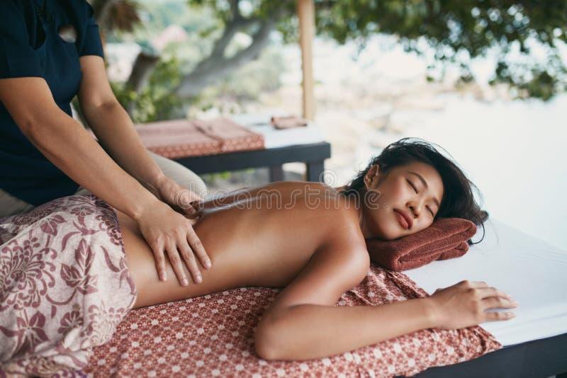 Rückenmassage am thailändischen Badekurort Frau, die Körper-Massage am Salon hat lizenzfreie stockbilder