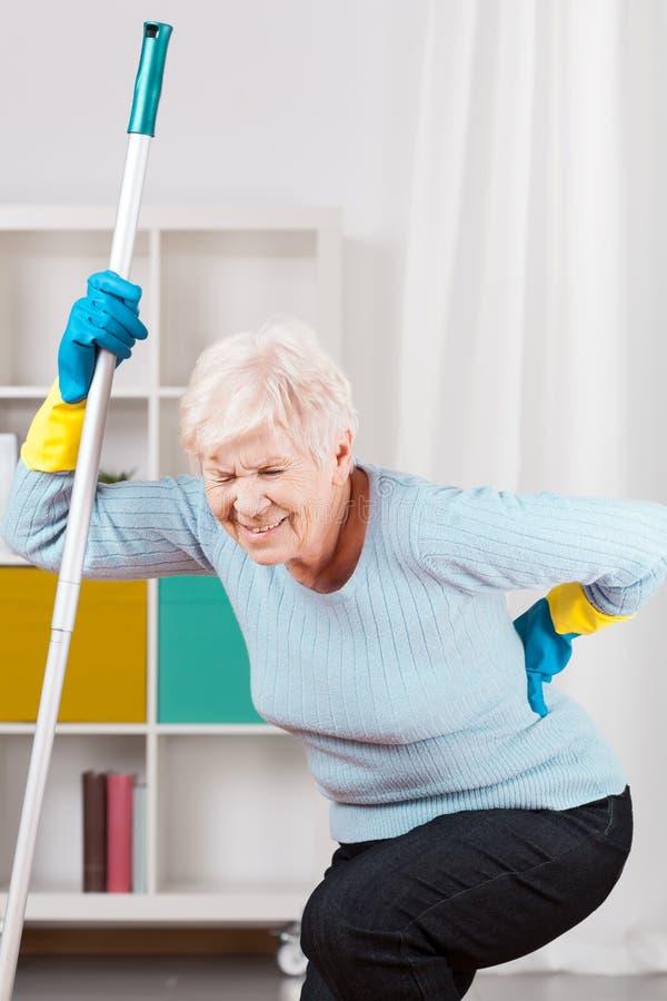Rückenschmerzen während aufräumen stockbild