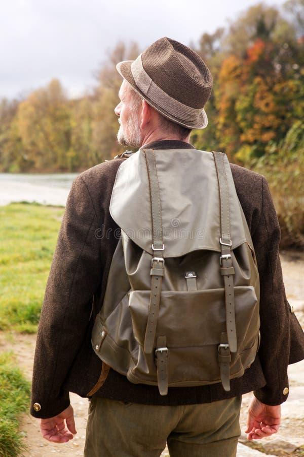Rückseite des bayerischen Mannes mit bereitstehendem Fluss des Rucksacks stockbild