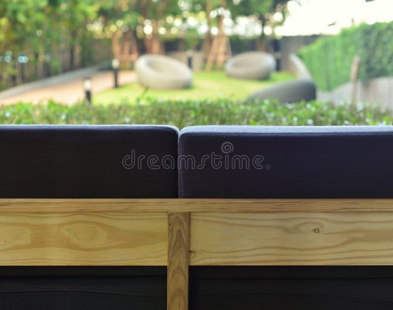 Rückseite des Sofas und des undeutlichen Gartens, im Freien lizenzfreie stockbilder