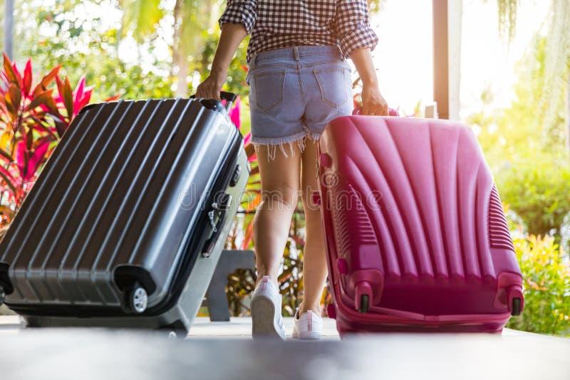 Rückseite und Beine von den Frauen, die mit Koffern mit einem hellen exotischen Hintergrund gehen stockbilder