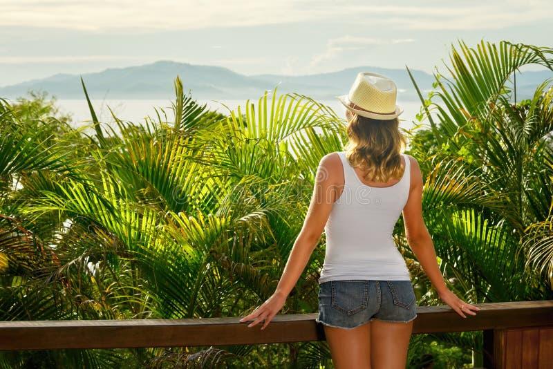 Rückseiteansicht über wunderbare junge Frau im Hut auf Terrasse stockbild