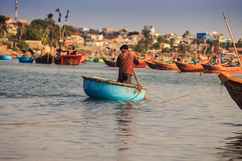 Rückseiten-Ansicht Guy Rows in rundes Fischerboot im ruhigen See stockbilder