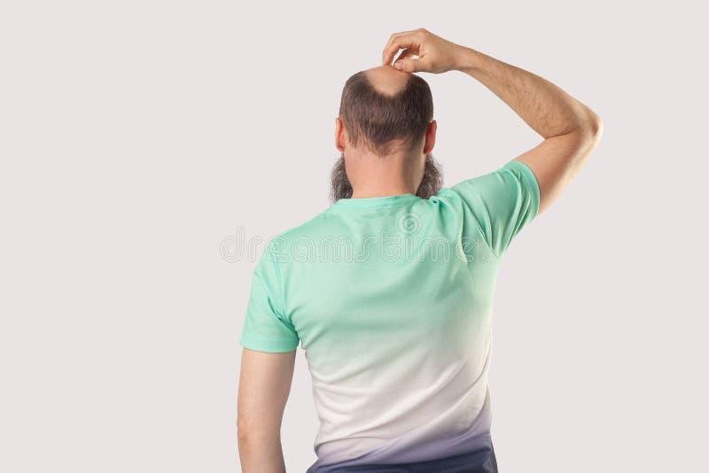 Rückseitenporträt der Mitte alterte kahlen Mann mit Bart in hellgrüner T-Shirt Stellung, verkratzte seinen Kopf oder ungefähr den lizenzfreies stockfoto