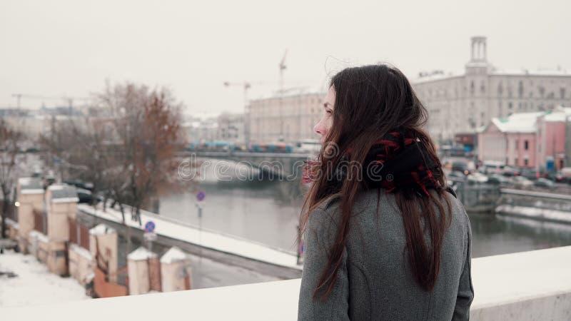Rückseitige Ansicht Attraktives junges Brunettemädchen, das auf der Brücke und den Blicken an der schneebedeckten Winterstadt ste stockfotografie