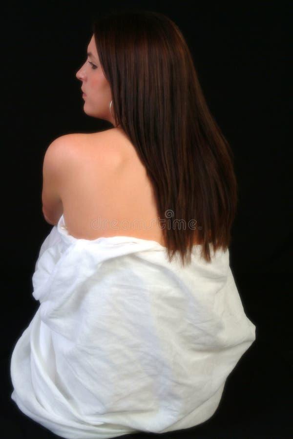 Rückseitige Ansicht der Frau drapierte im weißen Blatt stockfoto