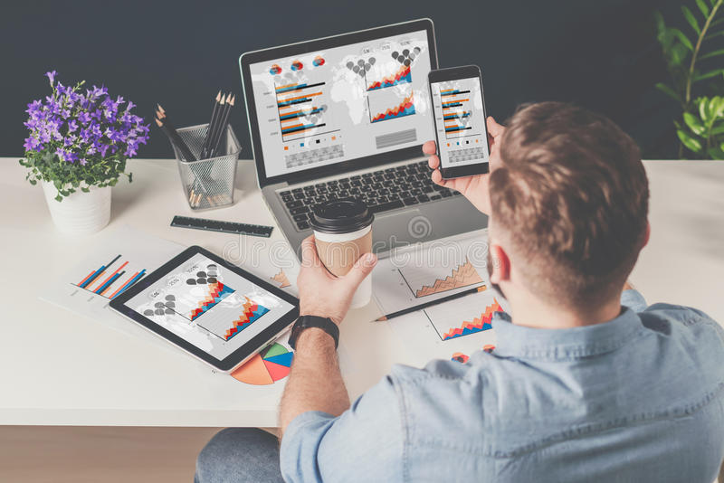 Rückseitige Ansicht Junger bärtiger Geschäftsmann im Denimhemd sitzt im Büro bei Tisch und benutzt Smartphone mit Diagrammen, Dia stockbilder