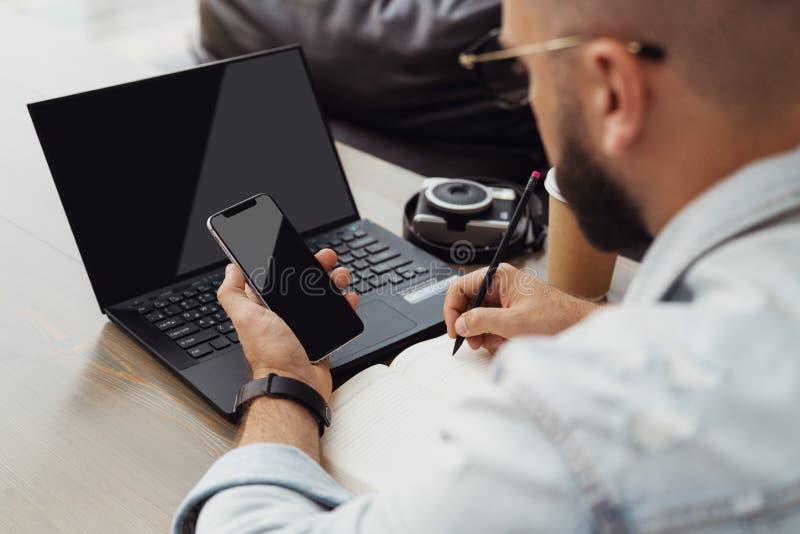 Rückseitige Ansicht Modische Gläser des jungen bärtigen Mannes sitzt Caféfront der Laptop-Computers, benutzt Smartphone, nimmt Ke stockfoto