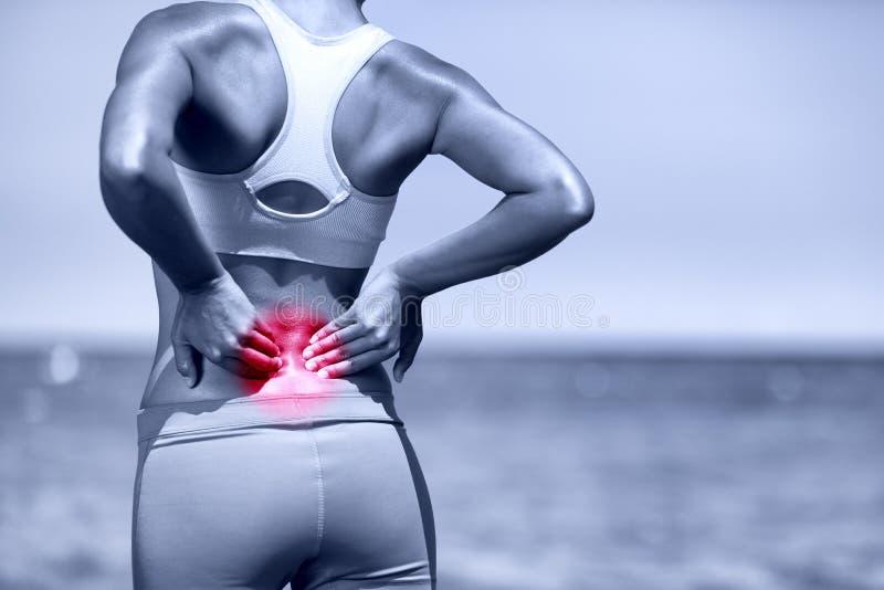 Rückseitige Schmerz Athletische laufende Frau mit Rückenverletzung stockbild