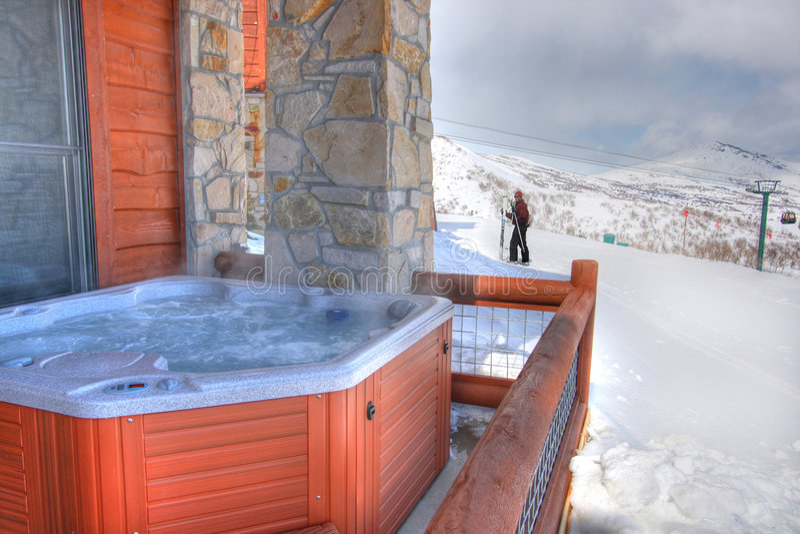 Rückseitiger Patio eine heiße Wanne und ein Skifahrer stockfoto