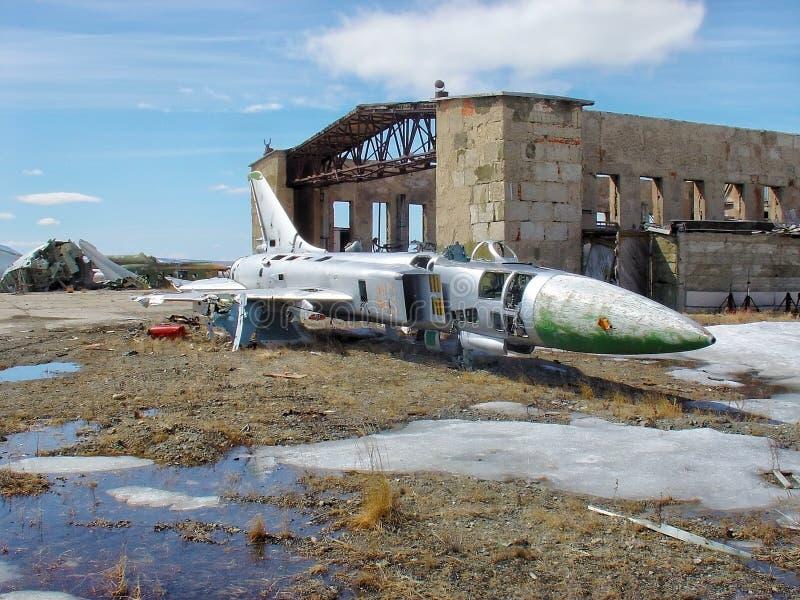 Rückstand Weinlesedes sowjetischen Militärkämpferflugzeuges, das draußen am Altmetalllagerhaus auf gesprengtem Gebäude und blauem lizenzfreie stockfotos