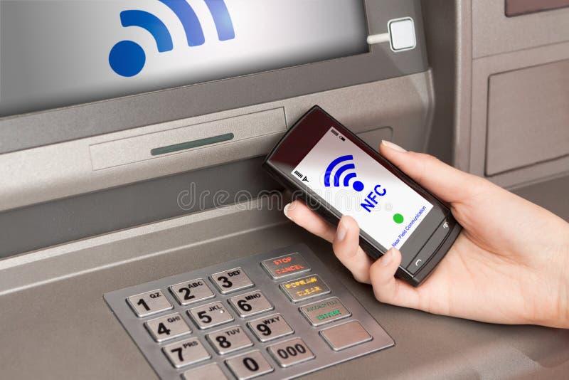 Rückzug Geld-ATM mit Handy ein NFC-Anschluss stockbilder