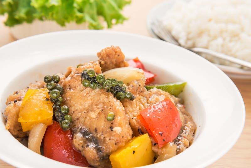 Rühren Sie gebratene Fische in der Soße des schwarzen Pfeffers auf Platte und Reis stockbild