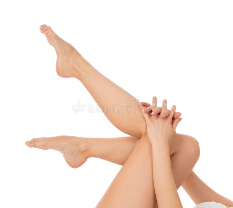 Rührende Hände und Beine der Frau mit Franzosen manikürten Nägel stockbilder