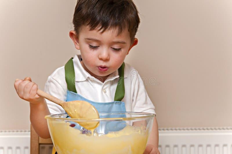 Rührende Kuchenmischung des Jungen in einer Glasschüssel lizenzfreies stockfoto