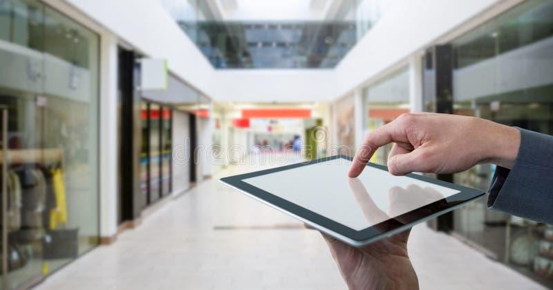 Rührende Tablette des Geschäftsmannes im Einkaufszentrum lizenzfreie stockfotos