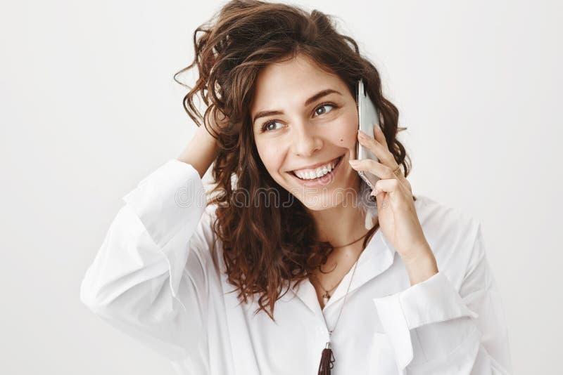 Rührendes Haar der glücklichen europäischen Frau bei der Unterhaltung auf Smartphone, beiseite schauend mit breitem Lächeln und p stockbilder