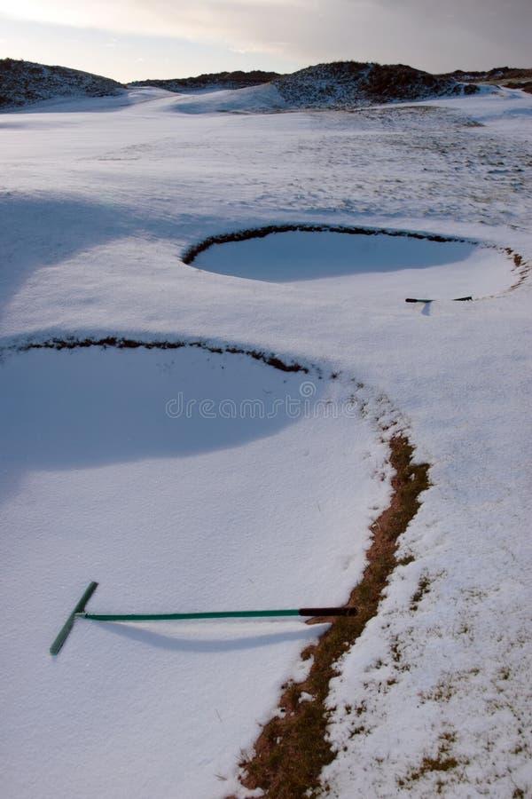 Rührstangen in den Bunkern auf einem Schnee umfaßten Golfplatz stockfotografie