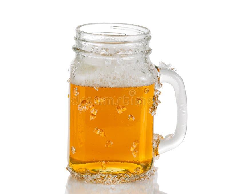 Rütteln Sie das Glas, das mit eiskaltem bernsteinfarbigem Bier auf weißem Hintergrund gefüllt wird stockfoto