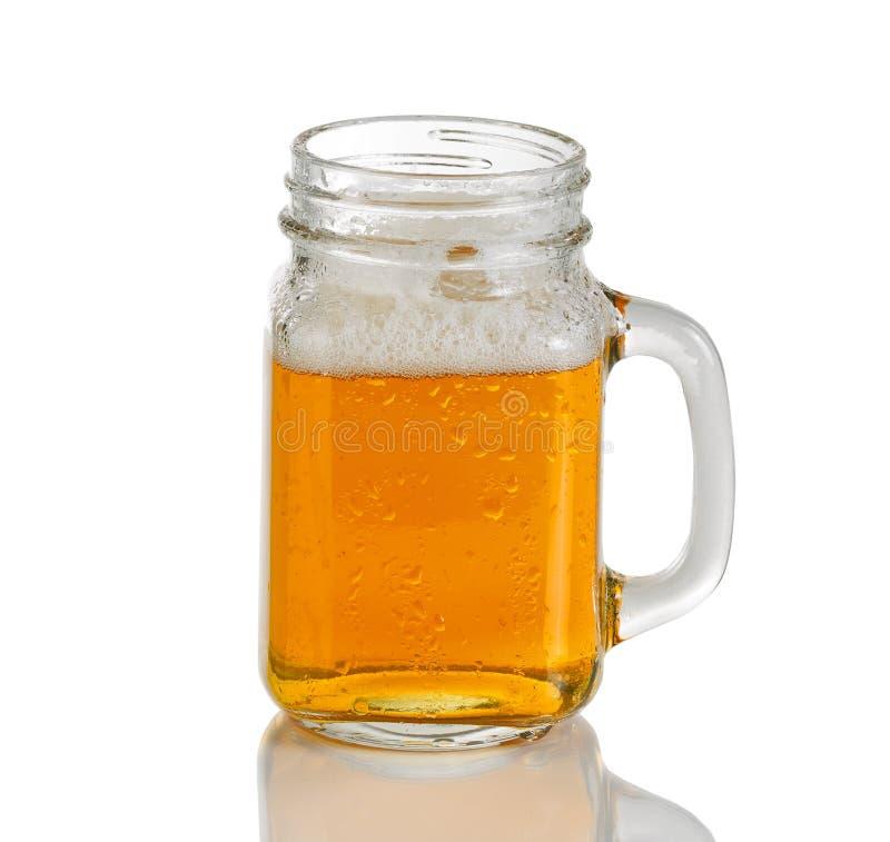 Rütteln Sie das Glas, das mit kaltem bernsteinfarbigem Bier auf weißem Hintergrund gefüllt wird stockfoto
