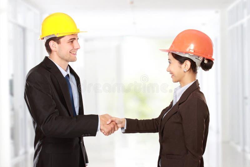 Rütteln von Händen an der Baustelle lizenzfreie stockfotos