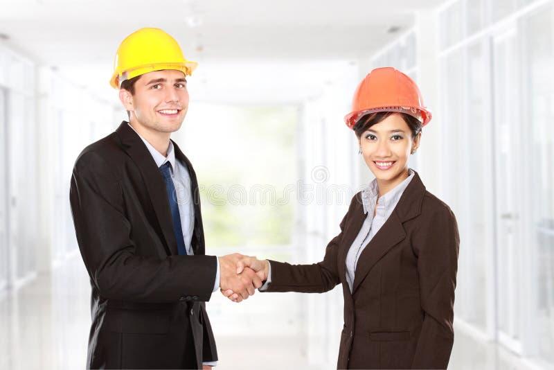 Rütteln von Händen an der Baustelle stockbild