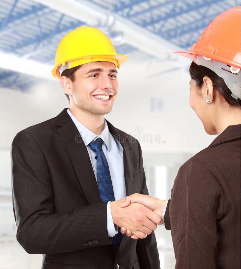 Rütteln von Händen an der Baustelle lizenzfreies stockbild